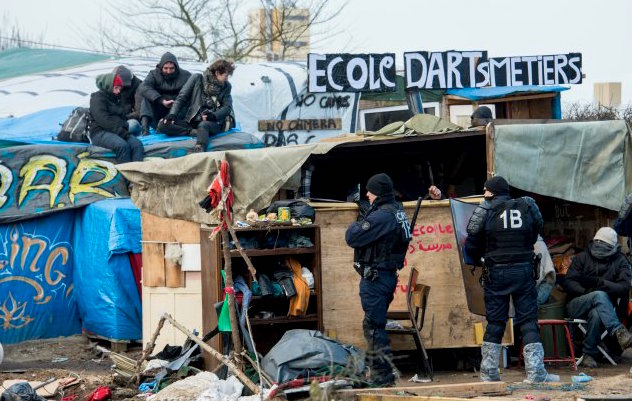 "© DENIS CHARLET / AFP | French riot police keep watch during the end of the dismantling of the southern part of the so-called ""Jungle"" migrant camp in Calais, northern France, on March 16, 2016"